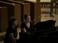 Accompanist and her page turner sit at the piano