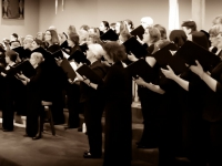 Black and white photo of the chorus, in all black, holding folders singing