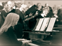 black and white photo of the accompanist at the piano with the chorus singing in the background