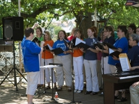 The chorus sings at Central Market under the shade of a big tree